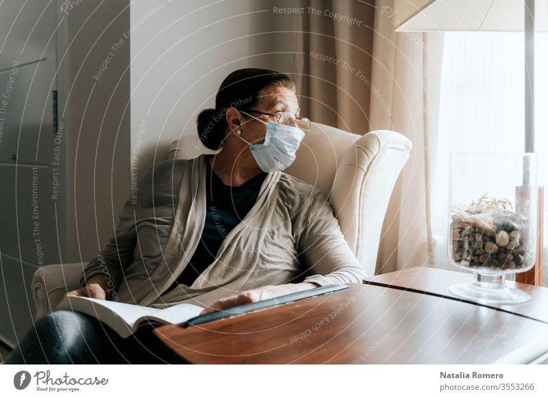 Eine ältere Frau sitzt auf dem Sofa mit einem Buch auf den Beinen. Sie schaut durch das Fenster. Sie ist krank und trägt eine Schutzmaske. Sie schützt ihre Familie. Pandemie-Konzept.