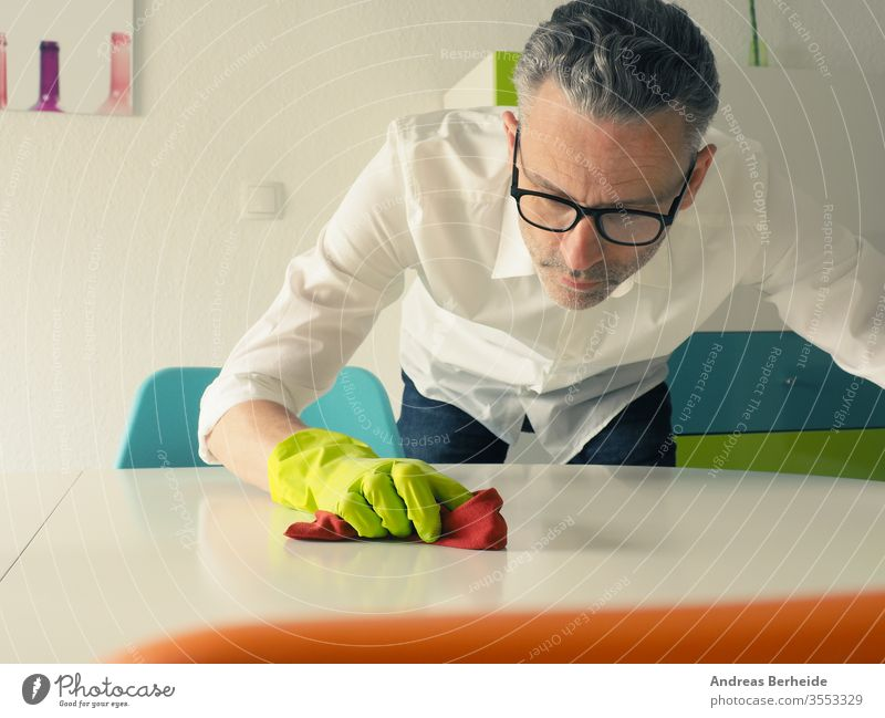 Mann mittleren Alters reinigt gründlich einen weißen Esstisch Tisch Reinigen Perfektion Ehemann wirklich im Innenbereich übersichtlich Lifestyle manuell