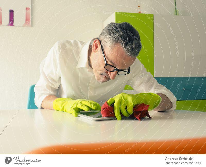 Mann mittleren Alters reinigt einen Tablet-Computer gründlich Erwachsener attraktiv bärtig Kaukasier Hausarbeiten Sauberkeit Raumpfleger Reinigen Tablette