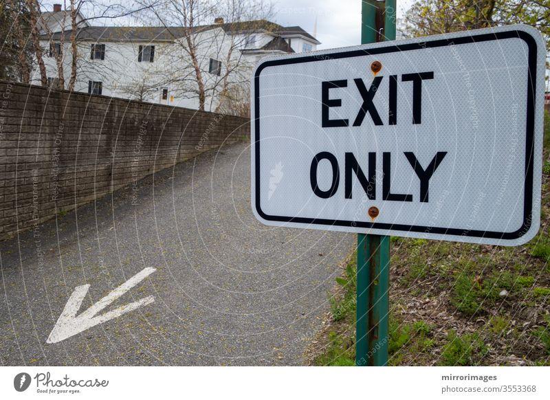"""Vorstadtgebiet mit Ausfahrtsstraße mit aufgemaltem Pfeil auf dem Asphalt und grünem Pfahl schwarz-weißes Schild mit der Aufschrift """"Exit Only""""."""