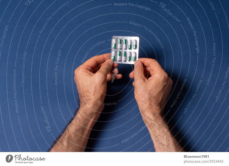 Ein Mann hält in den Händen einen kleinen Laib Kapselpillen vor einem dunkelblauen Hintergrund Tablette Single Beteiligung durch Finger männlich Menschen