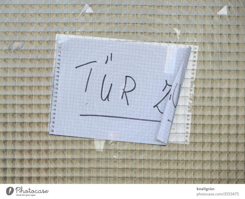 Drahtglasscheibe einer Hautür mit angeklebtem karierten DIN A4 Blatt, an einer Seite leicht eingerollt, mit der Aufschrift TÜR ZU Schilder & Markierungen