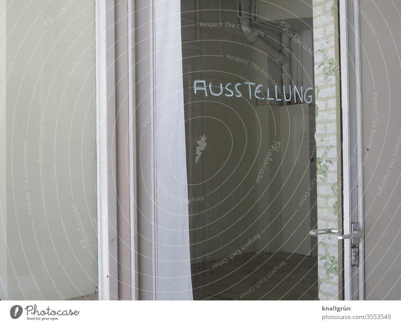 Triste Galerie, auf deren verglaster Eingangstür das handgeschriebene Wort AUSSTELLUNG steht Ausstellung Tür Kunst Menschenleer Außenaufnahme Glastür trist weiß