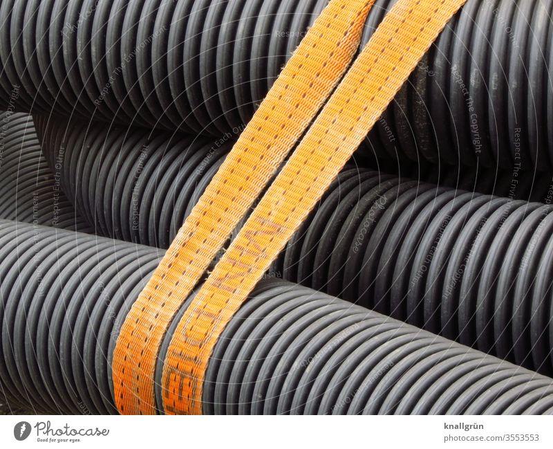 Mehrere Drainagerohre von einem doppelten braunen Gurt zusammen gehalten Rohre Detailaufnahme Farbfoto schwarz grau Rillen Muster Streifen Strukturen & Formen