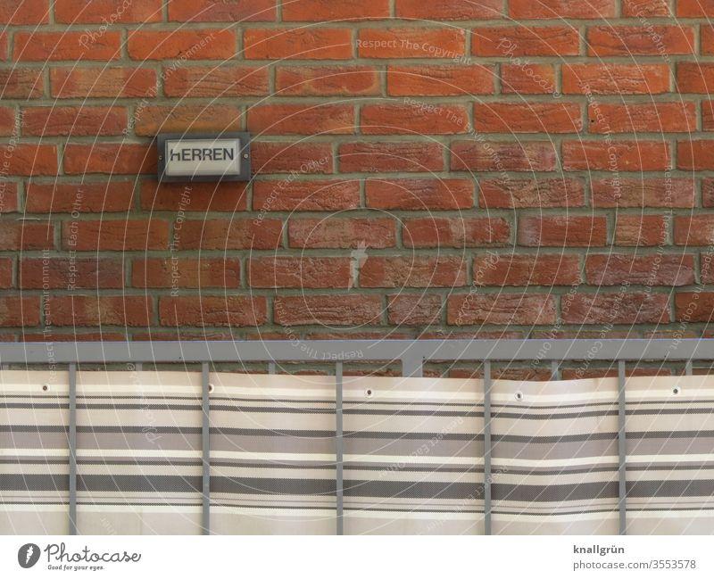 Kleines Hinweisschild HERREN an roter Ziegelwand, davor ein Metallgeländer mit gestreiftem Markisenstoff Schilder & Markierungen Herrentoilette Außenaufnahme