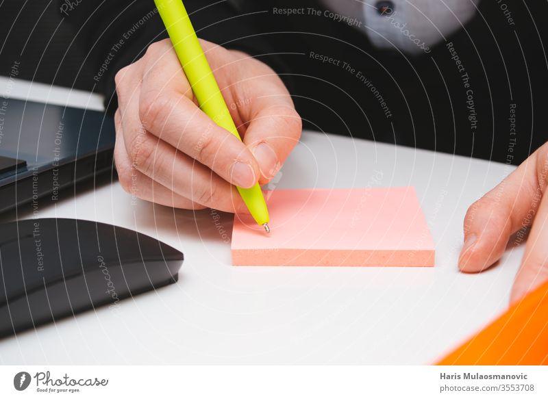 Handschrift mit Stift auf dem rosa Aufkleberzettel im Büro in Nahaufnahme Erwachsener Hintergrund Holzplatte Gebäude Business abschließen Farben Computer