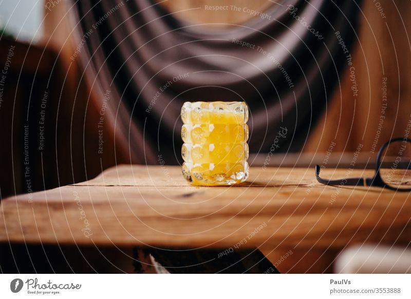 Glas mit Orangensaft auf Holztisch orangensaft frühstück pause saftglas vitamine vitamin c ernährung gesund urlaub frucht lebensmittel smoothie getränk