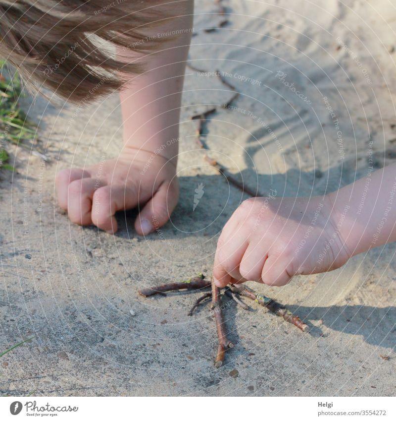 Kreativität ausleben - Detailaufnahme, kleiner Junge  legt im Sand einen Pfeil aus Stöckchen Kind Kindheit Kleinkind Mensch Arm Hand Haare Spielplatz Sommer