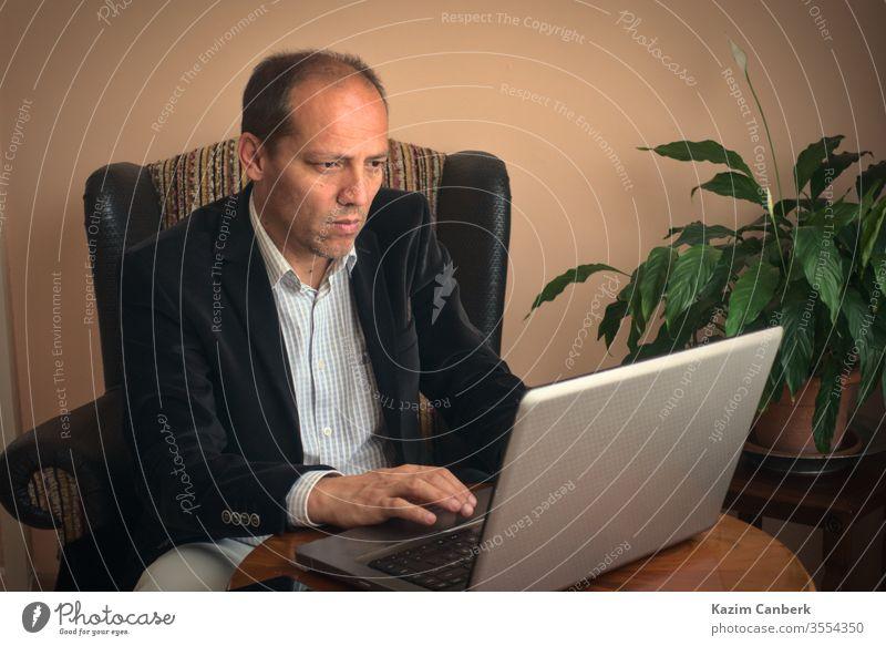Älterer erwachsener Mann, der von zu Hause aus mit seinem Laptop mit Pflanze im Hintergrund arbeitet Arbeit von zu Hause aus älterer Mann Telearbeit heimwärts