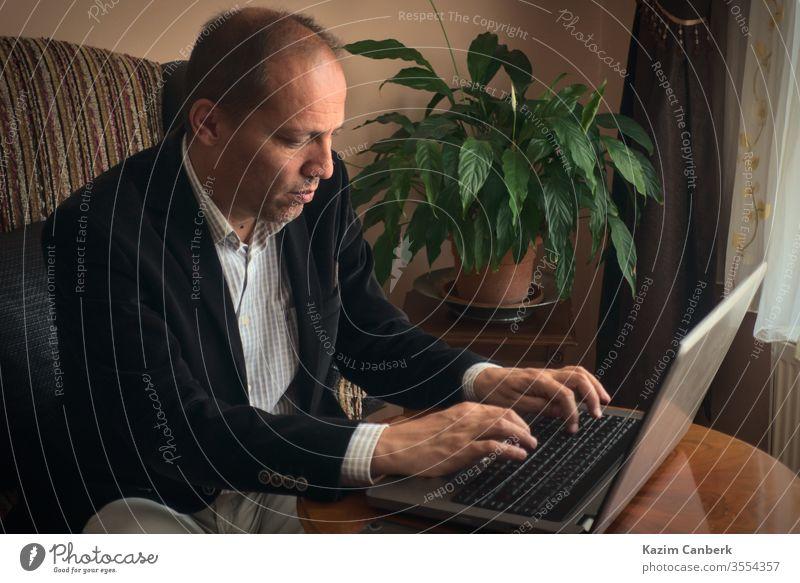 Schwerer männlicher Erwachsener, der von zu Hause aus arbeitet und am Laptop mit einer Pflanze auf dem Hintergrund tippt Arbeit von zu Hause aus älterer Mann
