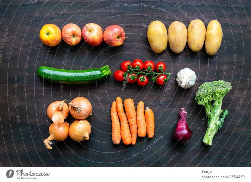 Frisches regionales Gemüse in einer Reihe auf einem braunen Holz Hintergrund, Draufsicht bunt Gemüsekiste Lebensmittel Bioprodukte Vegetarische Ernährung