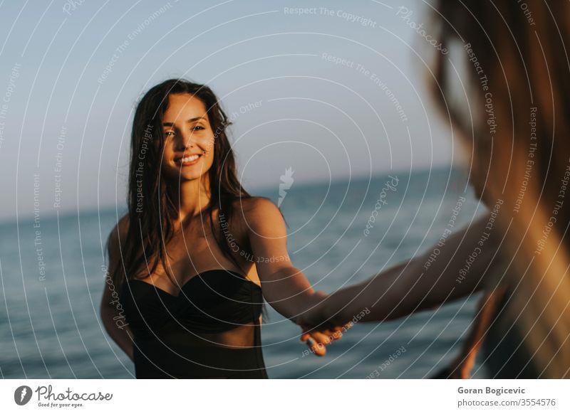 Junge Frauen amüsieren sich in den Sommerferien am Strand schön zwei Menschen attraktiv MEER Urlaub Lifestyle Spaß Glück Wasser Freunde jung Mode Freundschaft