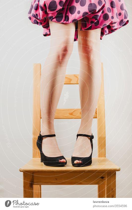Selektive Aufnahme von weißen Frauenbeinen in schwarzen hochhackigen Schuhen, die auf einem Holzstuhl stehen. kostümiert Spaß Körper gesichtslos getönt Menschen