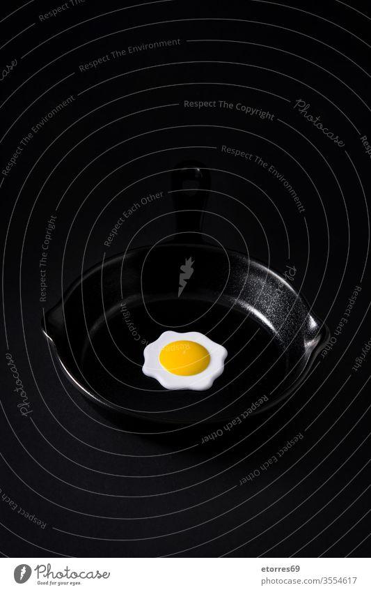 Schwarze Bratpfanne mit Ei innen auf schwarzem Hintergrund Konzept Geschirr getrocknet leer Lebensmittel bügeln vereinzelt Küche Minimalismus Attrappe Objekt