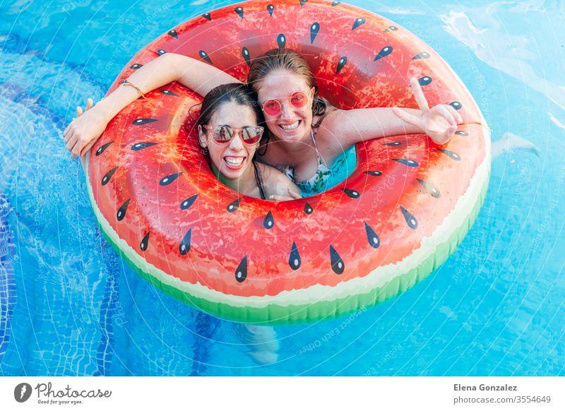 Zwei Freunde mit Sonnenbrille im aufblasbaren Wassermelonenring. Junge Frauen genießen den Sommer am Swimmingpool. Hand-Siegeszeichen-Geste. Spaßige Zeit Damen