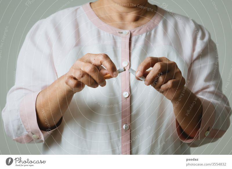 Raucherentwöhnung, kein Tabaktag, Mutterhände brechen die Zigarette Süchtige Erwachsener gealtert Anti Hintergrund schlecht schön gebrochen Pflege Kaukasier