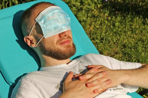 junger Mann liegt auf Sonnenliege und hat eine Atemschutzmaske vor den Augen Schutzmaske Augenschutz Hygiene Sonnenschutz Vorsichtsmaßnahme Gefahr erholen