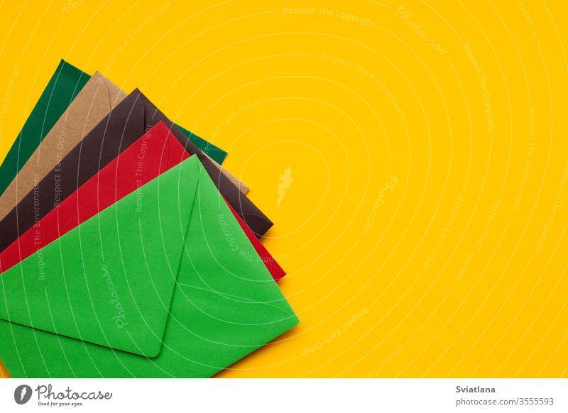Roter, brauner, grüner Umschlag auf gelbem Hintergrund, mit Platz für Text, Ansicht von oben Business Design Farbe Sommer Textur Geburtstag Büro Schot Papier