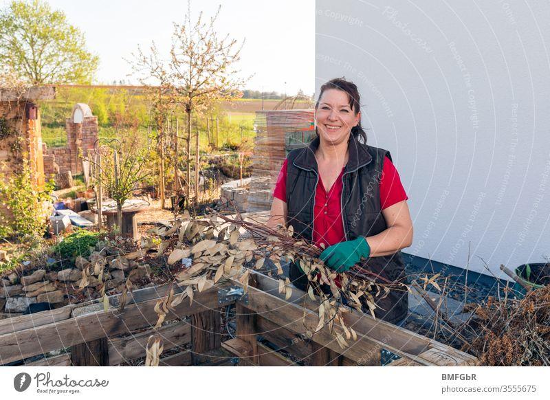 Frau beim Anlegen eines Hochbeetes Garten Gartenarbeit lachen lächeln Paletten Gartenhandschuhe Natur entspannen hobbygärtner Freizeit & Hobby Umwelt