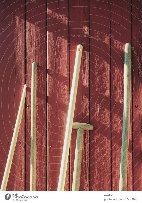 Stielvoll Wand Gartenlaube schwedenrot Bretterwand Farbe gestrichen rostrot Sonnenlicht Schatten Besen Schaufel Werkzeug Geräte Gartengeräte Gartenarbeit Stiele