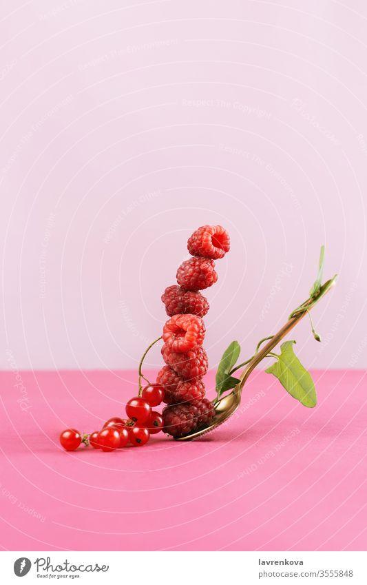 Ausgleichender Stapel frischer Rapsfrüchte auf einem goldenen Löffel mit grünen Efeublättern, selektiver Fokus rosa Gleichgewicht Konzept Himbeeren Blätter