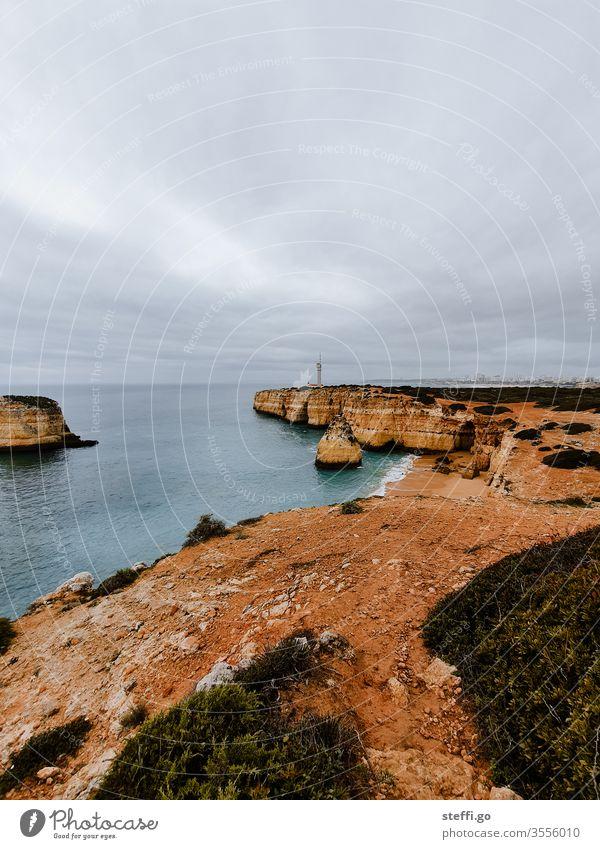 Ausblick über eine Bucht an der Algarve mit Felsküste und Leuchtturm Ferragudo Felsen Felswand Küste Meer Außenaufnahme Farbfoto Menschenleer Wellen