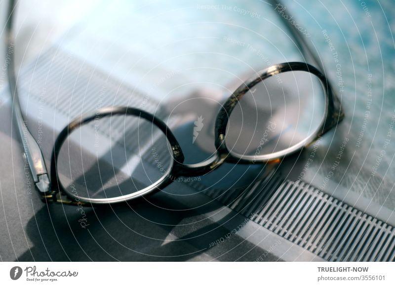 Genau betrachtet handelt es sich um eine Brille, auf einem Magazin liegend, dessen Titel eine Wassernixe mit Badekappe zeigt, die am Schwimmbeckenrand in der Sonne sitzt und einen starken Schatten wirft