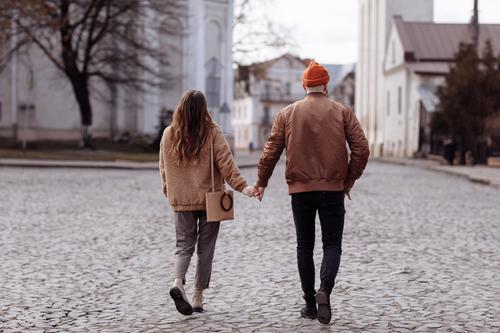 Liebesgeschichte des schönen jungen Mannes und der schönen jungen Frau, die unter freiem Himmel in der Stadt spazieren gehen. Umarmung bei einem Stadtspaziergang. Kopierraum.