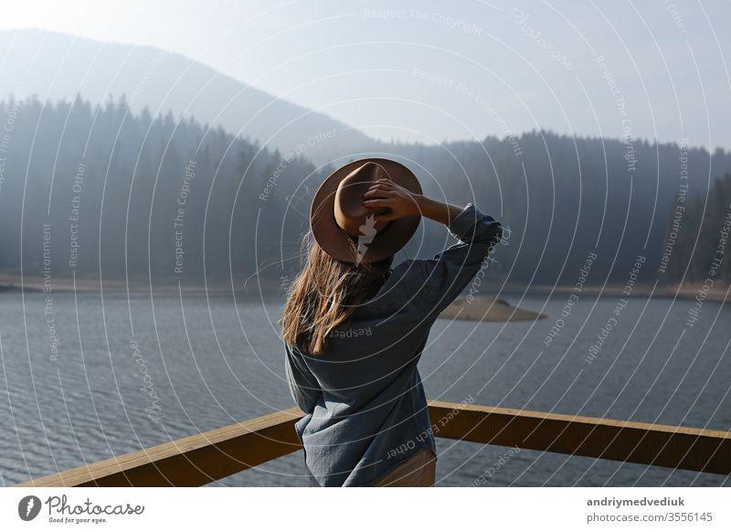 glückliche junge Frau mit Hut genießt Seeblick in den Bergen . Entspannende Momente im Wald. Rückansicht des stilvollen Mädchens genießt die Frische im Freien. Freiheit, Menschen, Lebensstil, Reisen und Urlaub