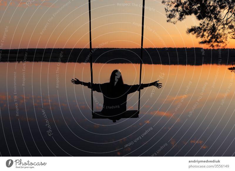 romantische junge Frau auf einer Schaukel über dem See bei Sonnenuntergang. Junges reisendes Mädchen auf der Schaukel sitzend in schöner Natur, Blick auf den See