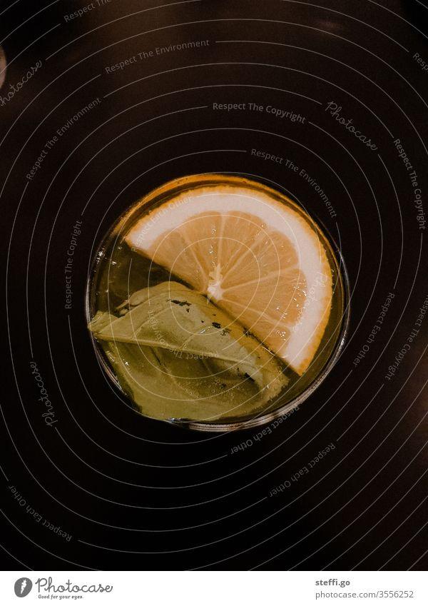 Glas mit einem Blatt und einer halben Zitronenscheibe von oben auf schwarzem Hintergrund Drink Trinkgefäß trinken Cocktail Longdrink Getränk Alkohol Farbfoto