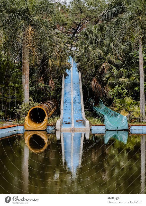 verlassene und verwilderte Wasserrutschen in einem Wasserpark im Dschungel mit Palmen in Vietnam lost places Hue Asien alt Menschenleer Farbfoto Verfall Tag