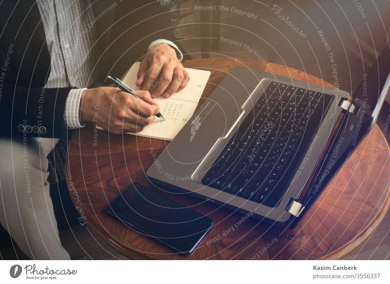 Älterer Mann macht Notizen mit Stift, während er mit seinem Laptop eine Telefonkonferenz führt Arbeit von zu Hause aus mitschreibend Hände Computer männlich