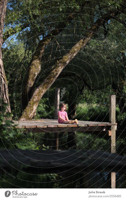 Kleinkind sitzt auf einem Steg zwischen Bäumen Saale Franken Holz Baum Weide Fluss Pflanze Natur Wasser Holzbretter Mädchen sitzen Blätter traumhaft natürlich