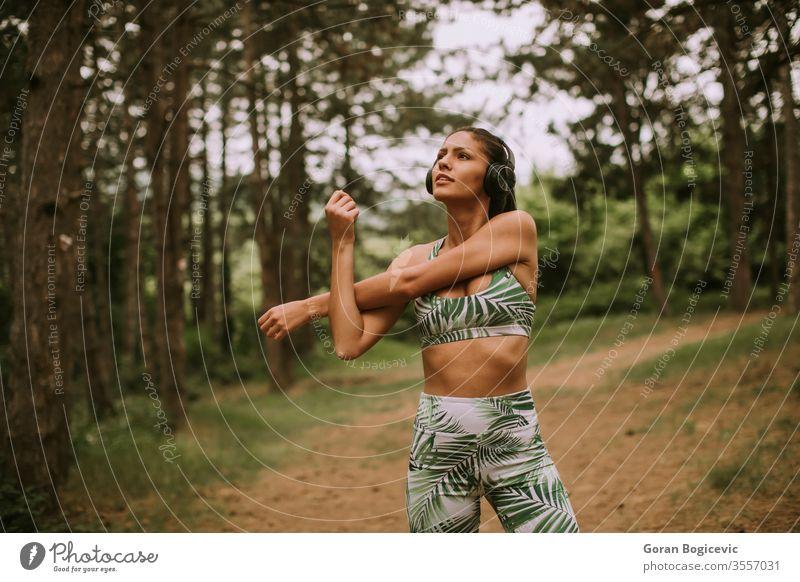 Junge Frau, die sich mitten im Wald beim Sport streckt und frische Luft atmet jung Übung Fitness Lifestyle Training Gesundheit Person Erwachsener sportlich