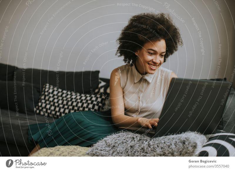 Attraktive junge Frau, die zu Hause am Laptop arbeitet Computer Menschen heimwärts professionell Person Business eine Technik & Technologie Afrikanisch
