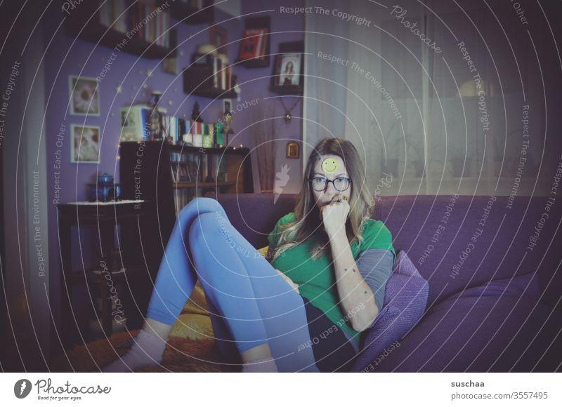 frau sitzt genervt in ihrem wohnzimmer und hat einen lachenden smiley auf der stirn (home office) Frau weiblich alleine Zuhause Wohnzimmer sitzen gelangweilt