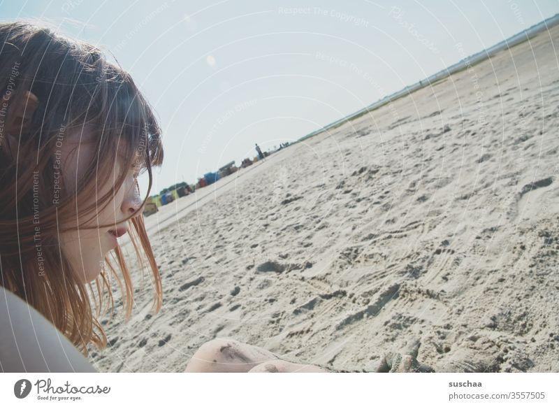 jugendliche sitzt an einem strand bei ebbe mit schiefem horizont Jugendliche Teenager Profil Gesicht Haare sitzen Sommer Sonne Strand Sand Meer Nordsee Ebbe