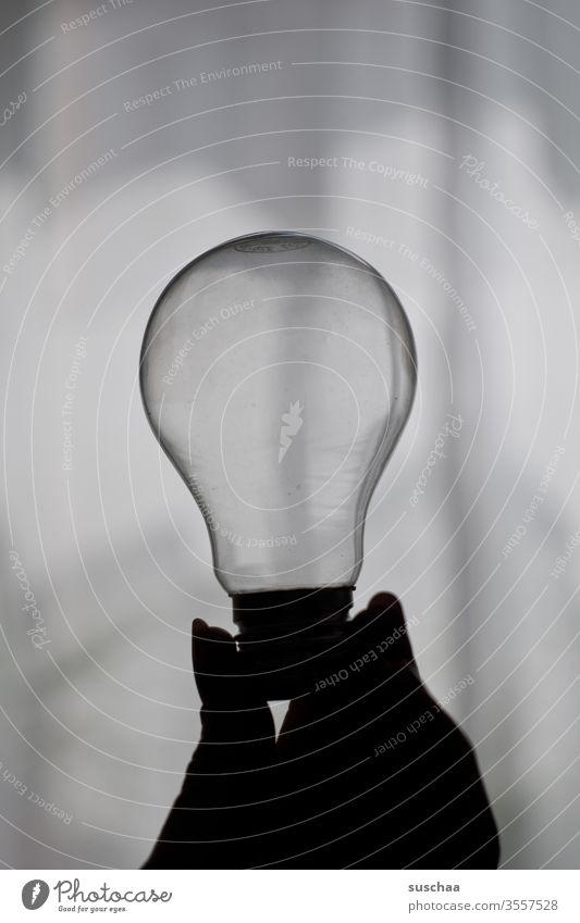 weibliche hand hält eine alte glühbirne Hand Finger Fingernägel Glühbirne Glas durchsichtig hell dunkel Licht und Schatten Umriss im Schatten Idee Einfall