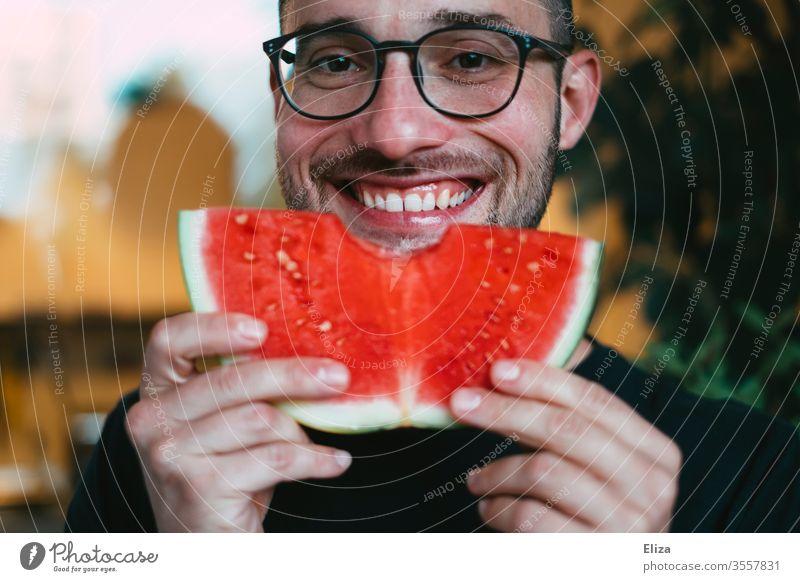 Ein Mann hält eine Scheibe Wassermelone hoch, in die er gerade reingebissen hat und lächelt dabei reinbeißen Biss lecker essen lächeln gesund fruchtig Freude