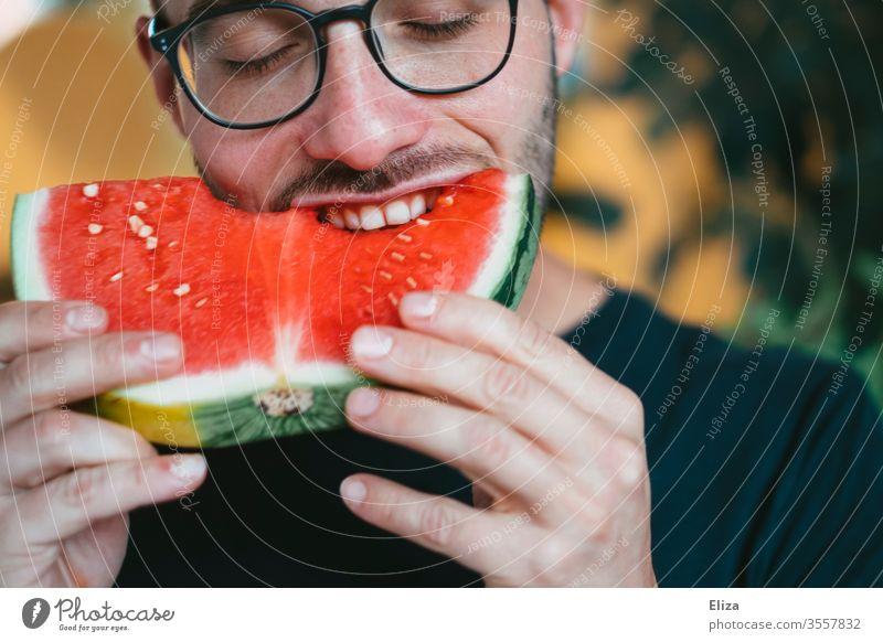 Ein Mann beißt in ein Stück Wassermelone reinbeißen Biss lecker essen lächeln gesund fruchtig Freude schlemmen Frucht saftig naschen Ernährung rot Gesundheit
