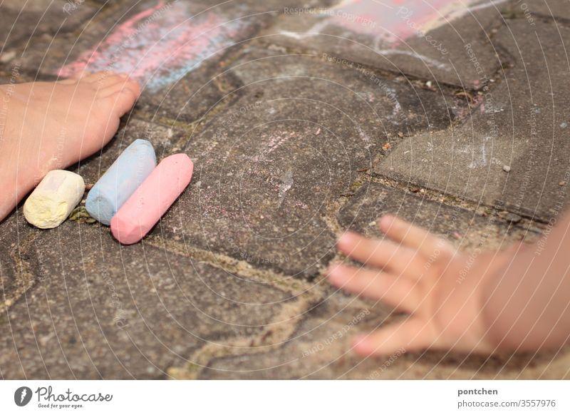 Zwei Kinder malen mit Straßenkreide. Kinderhand und Kinderfuß straßenkreide spiel kreativ hsbd bunt farben Kreativität Kindheit Freizeit & Hobby Spielen Freude