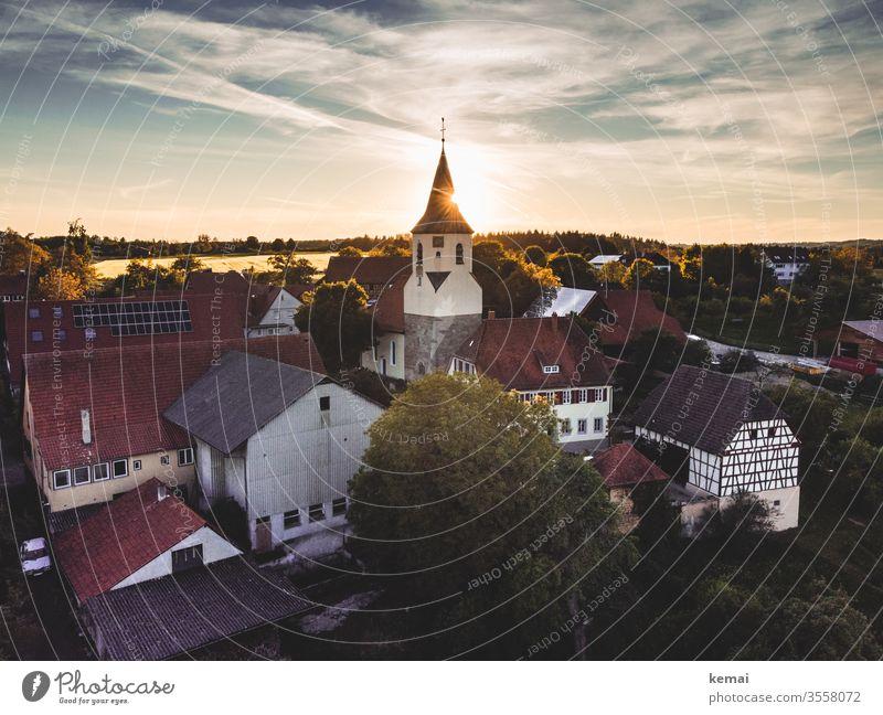 Dorf mit Dorfkirche im Abendlicht Drohnenansicht Drohnenaufnahme Licht Gegenlicht Sonne Sonnenlicht Abendsonne warm Land Ländlich Idylle Landleben Kirche