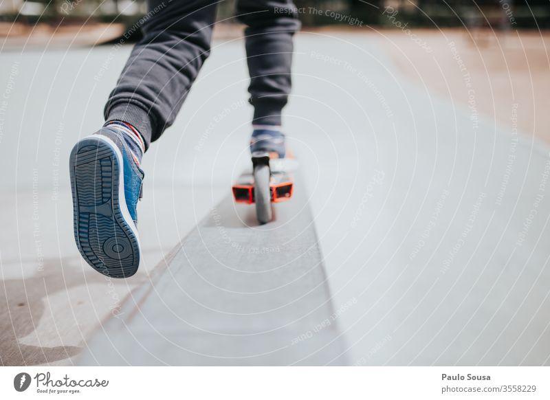 Kind spielt mit Roller Spaß Tretroller Park Menschen jung Kindheit Glück Fröhlichkeit Lifestyle Freude Porträt spielen niedlich im Freien heiter Sommer Schuhe