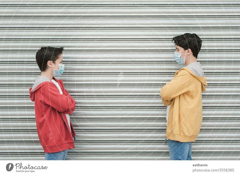 zwei Kinder mit medizinischer Maske halten soziale Distanzierung aufrecht Coronavirus Virus Seuche Pandemie Quarantäne Prävention Freundschaft Brüder Freunde