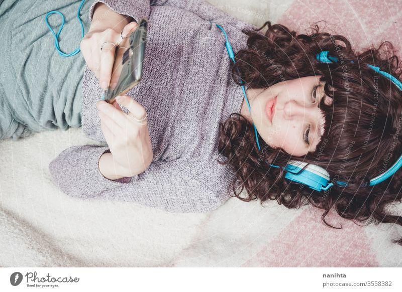 Junge brünette Frau, die in ihrem Schlafzimmer Musik hört Kopfhörer genießen Jugend hören Musik hören Freizeit Hobby zu Hause Quarantäne Technik & Technologie