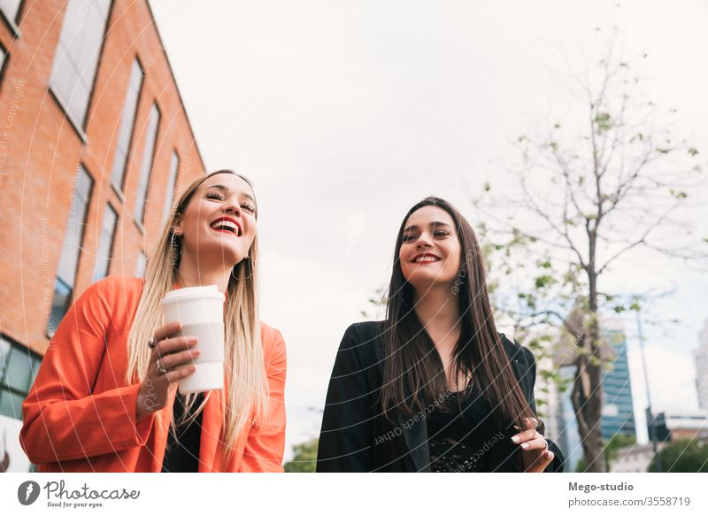Zwei junge Freunde, die zusammen im Freien spazieren gehen. zwei Straße Großstadt Lächeln hübsch sprechend Freundin Stadt Konzept Ansicht Stil reisen Wochenende