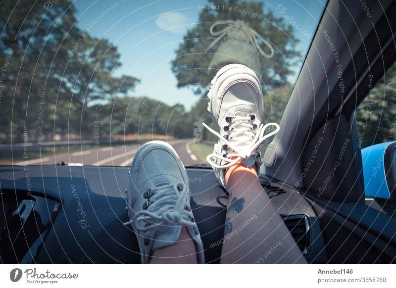 Freedom Car Travel-Konzept - Frau entspannt sich mit den Füßen auf dem Armaturenbrett und trägt weiße Turnschuhe. Sexy Frau im Auto. Hintergrund Mode PKW Baum