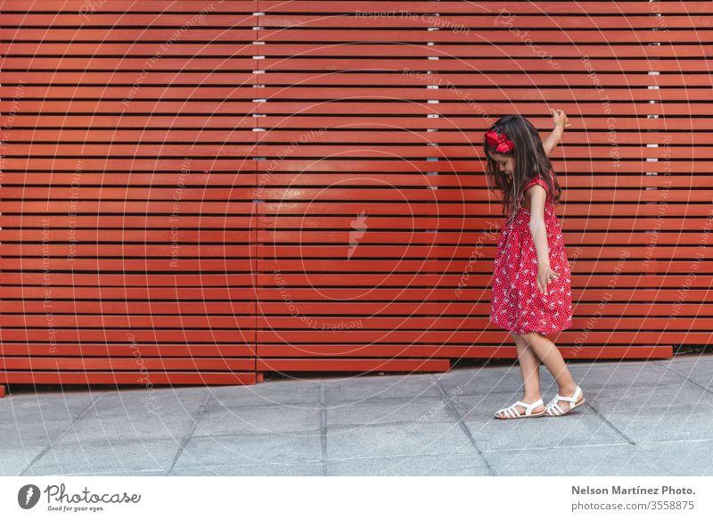 Glückliches kleines Mädchen mit weit geöffneten Armen vor rotem Hintergrund, ein rotes Kleid tragend. Sommer Spaß niedlich Kind lustig hispanisch