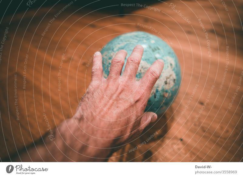 nach der Welt greifen - Hand greift nach einem Globus Größenwahn Mann Corona verbessern Ziel Geografie Weltreise Reiseziel Urlaub planung Urlaubsstimmung